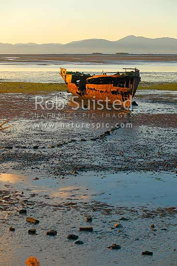 Wreck of the Jaine Seddon on Motueka foreshore. She was an Examination Vessel for Wellington Harbour during the World Wars and is said she fired the first shots of the WWII, Motueka, Tasman District, Tasman Region, New Zealand (NZ) stock photo.