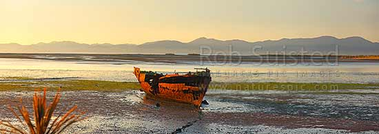 Wreck of the Jaine Seddon on Motueka foreshore. As an Examination Vessel for Wellington Harbour during the World Wars it's said she fired the first shots of the WWII. Panorama, Motueka, Tasman District, Tasman Region, New Zealand (NZ) stock photo.
