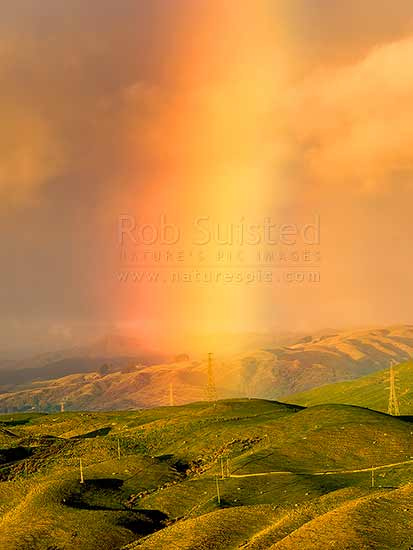 Rainbow over farmland and electricity powerlines above Porirua. Rainbow ahead of sooutherly weather change carrying rain. Belmont Regional Park, Porirua, Porirua City District, Wellington Region, New Zealand (NZ) stock photo.