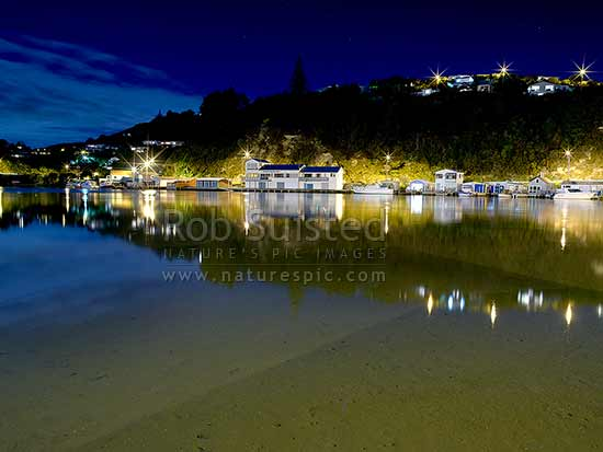 Paremata boatsheds on Porirua harbour Pauatahanui Arm inlet on a rising tide after dark. Ivey Bay far left, Paremata, Porirua City District, Wellington Region, New Zealand (NZ) stock photo.