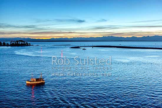 Nelson Haven and The Cut through the Boulder Bank, with a fishing boat returning to Nelson Haven and Port in twilight, Nelson, Nelson City District, Nelson Region, New Zealand (NZ) stock photo.
