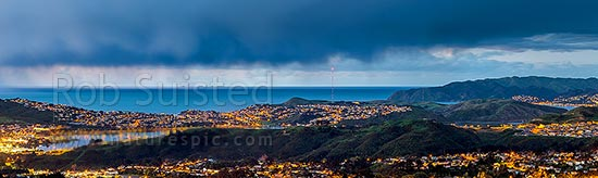 Porirua City (left) and Harbour at twilight. Porirua East and Cannons Creek in foreground, Takapuwahia and Titahi Bay and Cook Strait beyond, with Aotea, and Plimmerton at right. Panorama, Porirua, Porirua City District, Wellington Region, New Zealand (NZ) stock photo.