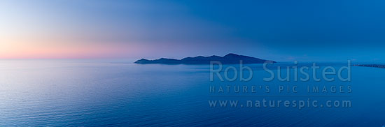 Kapiti Island at dusk. Rauoterangi Channel and Otaheke Strait separate the island 5kms from Paraparaumu Beach. Panorama, Paekakariki, Kapiti Coast District, Wellington Region, New Zealand (NZ) stock photo.
