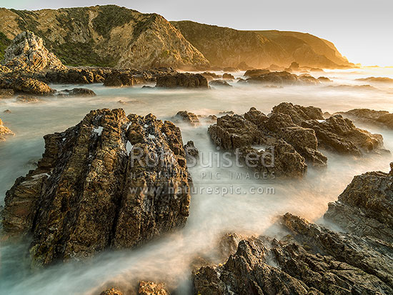 Whitireia Park coastline with blurred waves crashing over rocky shoreline in evening light, Titahi Bay, Porirua City District, Wellington Region, New Zealand (NZ) stock photo.