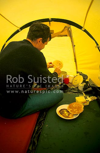 Bad weather outside again. Cooking pancakes in tent, Dale Creek, Mt Adams, Westland, Westland District, West Coast Region, New Zealand (NZ) stock photo.