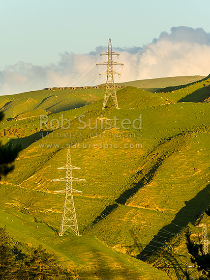 Power Pylons carrying national grid electricity over Belmont Regional Park hills and farmland. Historic WWII bunkers beyond, Belmont Regional Park, Porirua City District, Wellington Region, New Zealand (NZ) stock photo.