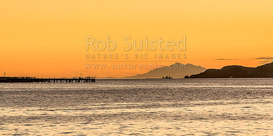 Wellington Harbour entrance sunset. Eastbourne wharf with fishers and South Island Seaward Kaikoura Ranges in distance. Seatoun and Point Dorset at right. Panorama, Eastbourne, Hutt City District, Wellington Region, New Zealand (NZ) stock photo.