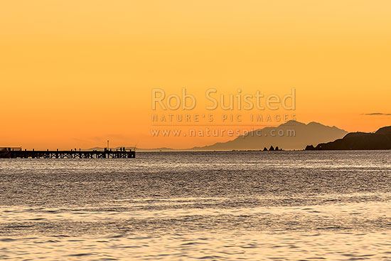 Wellington Harbour entrance sunset. Eastbourne wharf with fishers and South Island Seaward Kaikoura Ranges in distance. Seatoun and Point Dorset at right, Eastbourne, Hutt City District, Wellington Region, New Zealand (NZ) stock photo.