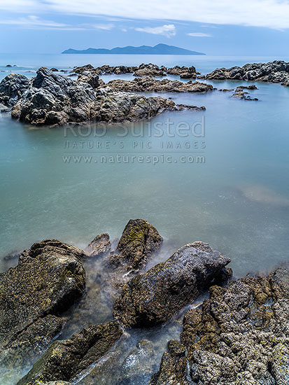 Kapiti Island and Cook Strait behind Pukerua Bay rocky coastline. Ethereal blurring of seawater and waves, Pukerua Bay, Porirua City District, Wellington Region, New Zealand (NZ) stock photo.
