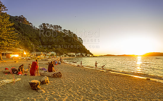 Days Bay Golden sunset looking out over Wellington Harbour. Families and friends enjoying a warm evening together swimming and socialising. Panorama, Days Bay, Hutt City District, Wellington Region, New Zealand (NZ) stock photo.