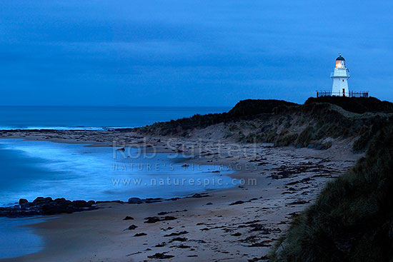 Waipapa Point lighthouse shining over beach on a moody twilight evening at last light, Fortrose, Southland District, Southland Region, New Zealand (NZ) stock photo.