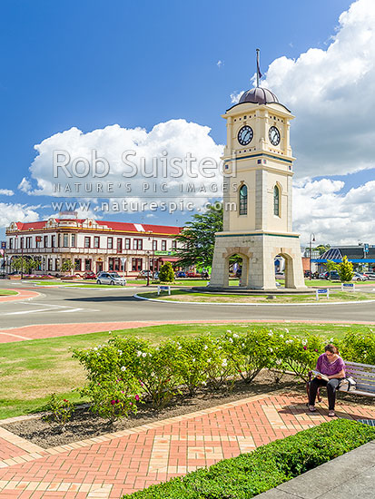Feilding town's clock tower. Feilding Hotel Building behind on Kimbolton Road. Woman reading in Manchester Square, Feilding, Manawatu District, Manawatu-Wanganui Region, New Zealand (NZ) stock photo.