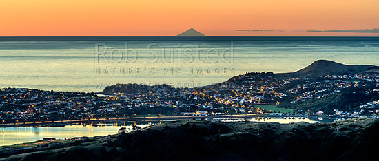 Porirua Harbour City, harbour and Titahi Bay, with Mt Taranaki on horizon across the Tasman Sea and South Taranaki Bight. Twilight panorama, Porirua, Porirua City District, Wellington Region, New Zealand (NZ) stock photo.
