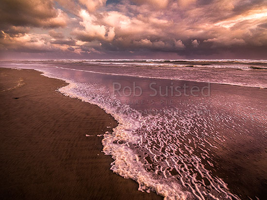 Wild west coast beach on a very moody evening with wind blown sea foam and brooding clouds, Aranga Beach, Manganui Bluff, Kaipara District, Northland Region, New Zealand (NZ) stock photo.