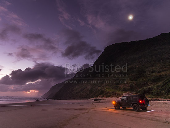 Aranga Beach below Maunganui Bluff and new moon, on a wild windswept moody dusk, with vehicle on sand, Aranga Beach, Manganui Bluff, Kaipara District, Northland Region, New Zealand (NZ) stock photo.