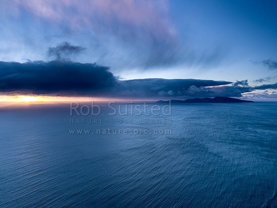 Kapiti Island Nature Reserve and moody dramatic sunset with sleety rainshowers coming off Cook Strait, Paekakariki, Kapiti Coast District, Wellington Region, New Zealand (NZ) stock photo.