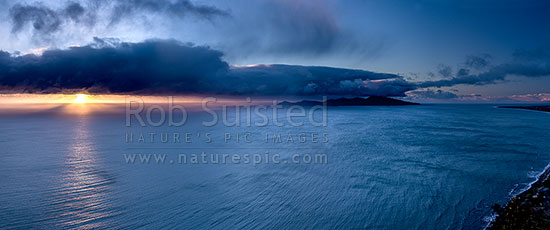 Kapiti Island Nature Reserve and moody dramatic sunset with sleety rainshowers coming off Cook Strait. Paraparaumu far right. Panorama, Paekakariki, Kapiti Coast District, Wellington Region, New Zealand (NZ) stock photo.