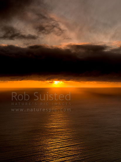 Cook Strait sunset through rainshower remnants and moody stormy clouds, creating crepuscular golden rays, Paekakariki, Kapiti Coast District, Wellington Region, New Zealand (NZ) stock photo.