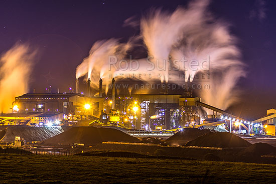 Glenbrook Steel Mill seen at night, producing steel from coastal ironsands ore, a unique utilisation. Steam billowing from stacks, Waiuku, Papakura District, Auckland Region, New Zealand (NZ) stock photo.