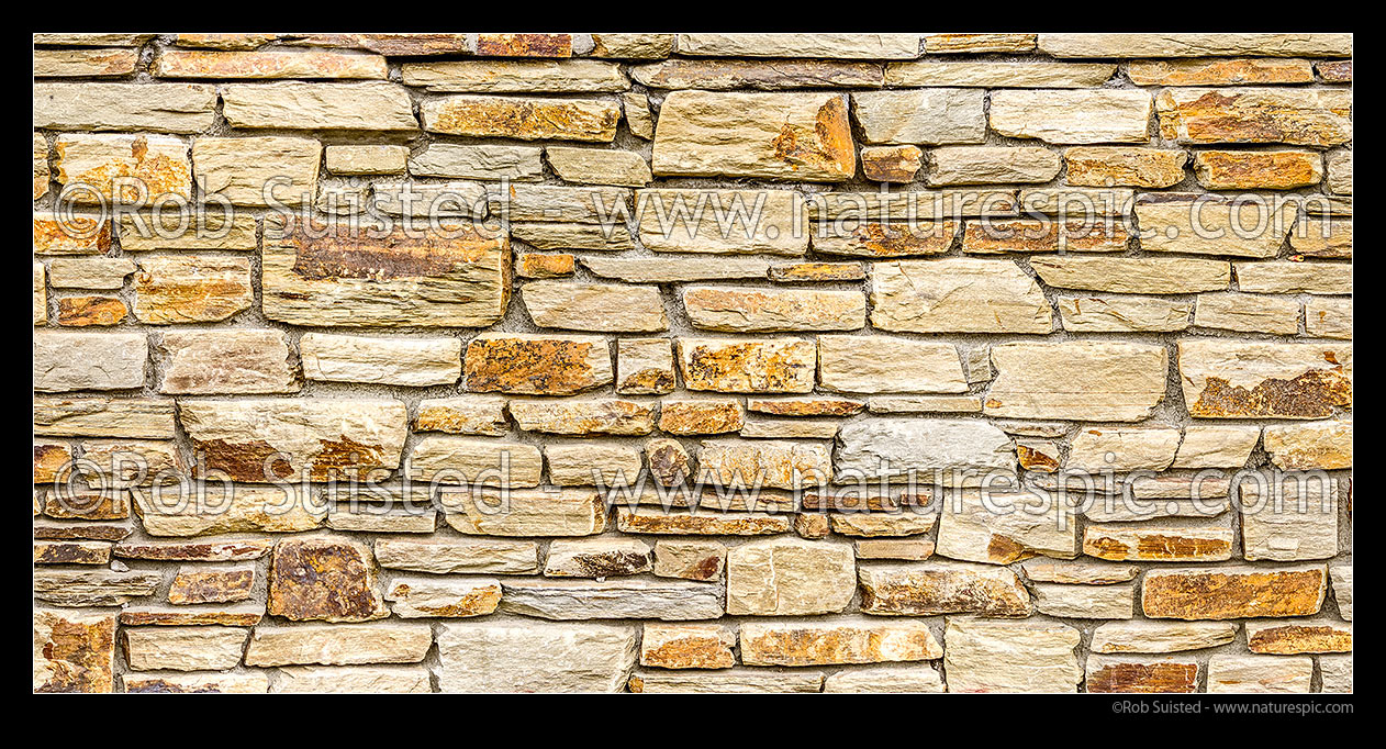 Schist stonewall. Schist rock layered into decorative stone wall ...