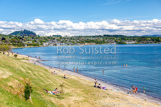 Lake Taupo waterfront and foreshore during summer. People enjoyng sunbathing and swimming, Taupo, Taupo District, Waikato Region, New Zealand (NZ) stock photo.