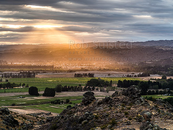 Alexandra town bathed in sunrise crepuscular rays. Seen from Earnscleugh, Alexandra, Central Otago District, Otago Region, New Zealand (NZ) stock photo.