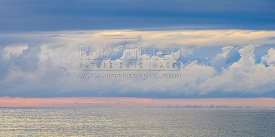 Long white cloud over the moody Tasman Sea. Seen from Bruce Bay on a calm evening. Panorama, South Westland, Westland District, West Coast Region, New Zealand (NZ) stock photo.