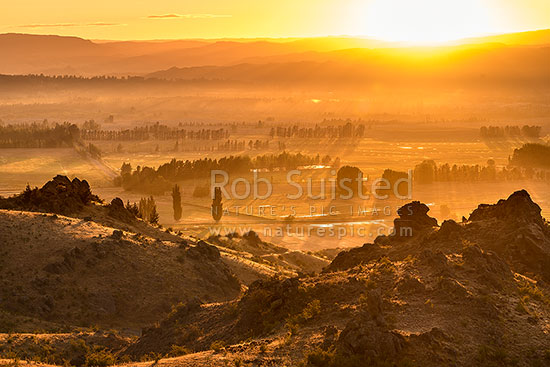 Central Otago sunrise over Earnscleugh and Blackmans, with Alexandra and the Clutha (Mata-Au) River plains beyond, Alexandra, Central Otago District, Otago Region, New Zealand (NZ) stock photo.