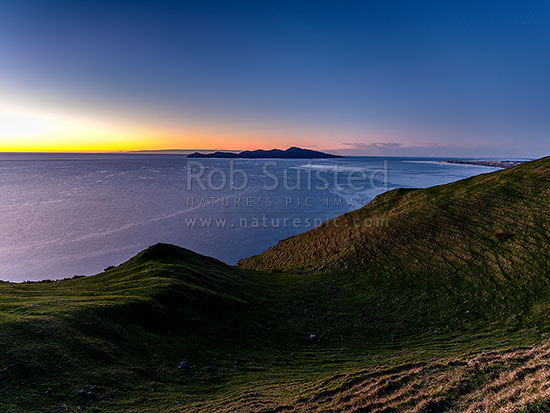 Kapiti Island at sunset, separated at sunset by Rauoterangi Channel and Otaheke Strait from Paraparaumu town and Mt Ruapehu at right distance, Paekakariki, Kapiti Coast District, Wellington Region, New Zealand (NZ) stock photo.