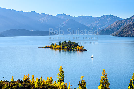 Lake Wanaka in autumn colours, with small boat sailing past Ruby Island, Wanaka, Queenstown Lakes District, Otago Region, New Zealand (NZ) stock photo.