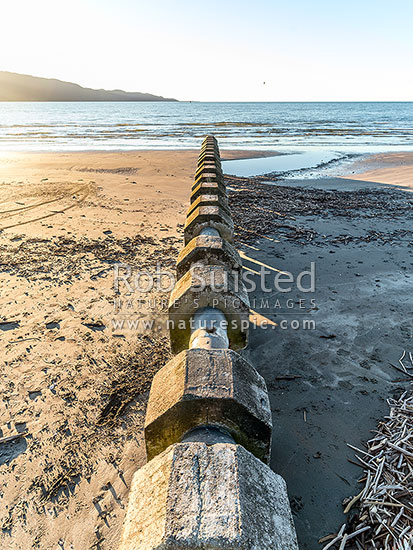 Stormwater drains, pipes and man holes exposed by sand erosion on beach. Kapiti Island behind, Paraparaumu Beach, Kapiti Coast District, Wellington Region, New Zealand (NZ) stock photo.