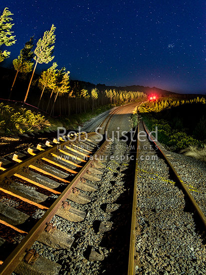 Papatea Fault rupture (marked with paint) pushed up railway and siding over 5 metres, previously tracks were flat and parallel. Kaikoura M7.8 earthquake. Railway lights still glowing in darkness, Waipapa Bay, Kaikoura District, Canterbury Region, New Zealand (NZ) stock photo.
