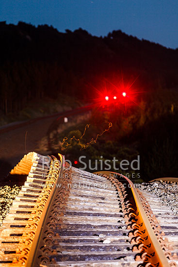 Railway tracks buckled upwards over 5 metres by the Papatea Fault rupture, leaving a major hill on previously flat line. Moths dancing in light, and railway signals still glowing. Kaikoura M7.8 earthquake, Waipapa Bay, Kaikoura District, Canterbury Region, New Zealand (NZ) stock photo.