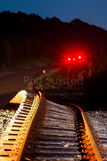 Earthquake buckled railway tracks pushed upwards over 5 metres by the Papatea Fault rupture, leaving a major hill on previously flat line. Railway signals still glowing in darkness. Kaikoura M7.8 earthquake, Waipapa Bay, Kaikoura District, Canterbury Region, New Zealand (NZ) stock photo.
