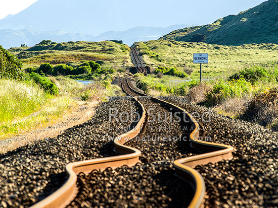 Earthquake buckled railway tracks. In background, the strike slip Kekerengu Fault has moved 9 metres left and pushed up a hill, on a dead straight and flat railway line. Kaikoura M7.8 earthquake, Tirohanga, Kekerengu, Kaikoura District, Canterbury Region, New Zealand (NZ) stock photo.
