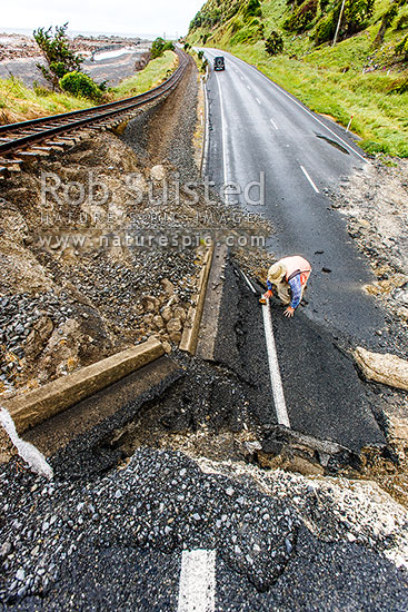 Earthquake damage to SH1 road and railway uplifted over 4 metres by the Papatea Fault rupture. Faultline visible entering sea behind. Kaikoura M7.8 earthquake, Waipapa Bay, Kaikoura District, Canterbury Region, New Zealand (NZ) stock photo.