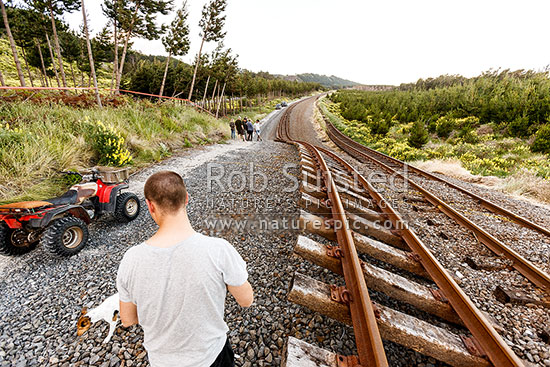 Rails, once flat and parallel, pushed up over 4 metres by Papatea Fault rupture. Homeless locals, displaced by landslide risk, meet returning travellers collecting abandoned vehicles. Kaikoura M7.8 earthquake, Waipapa Bay, Kaikoura District, Canterbury Region, New Zealand (NZ) stock photo.