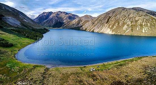 Lake Tennyson Scenic Reserve near the head of the Clarence River, inland Marlborough, with people camping on the shoreline. Crimea Range beyond. Aerial panorama, Molesworth Station, Hurunui District, Canterbury Region, New Zealand (NZ) stock photo.