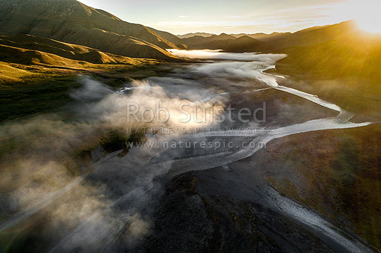 Clarence River braids under early morning fog, as it winds down past the Acheron confluence. Aerial view at sunrise, Molesworth Station, Marlborough District, Marlborough Region, New Zealand (NZ) stock photo.