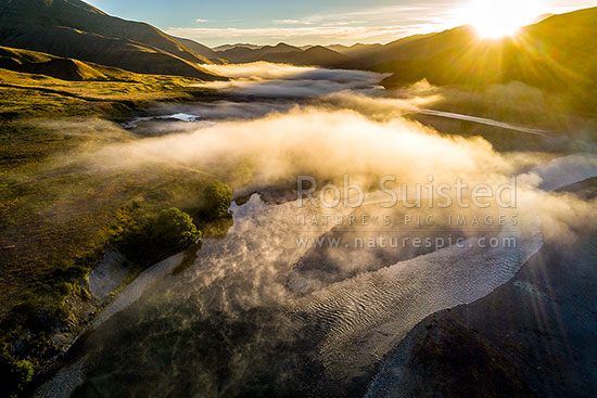Clarence River under early morning fog, as it winds down past the Acheron confluence. Aerial view at sunrise. Braided river, Molesworth Station, Marlborough District, Marlborough Region, New Zealand (NZ) stock photo.