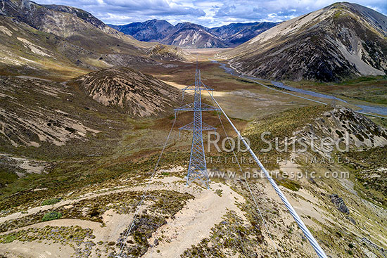 Powerlines and pylons carrying high voltage electricity over Island Saddle at 1360m. Looking down Serpentine Creek towards Clarence River. Wairau - Hanmer Springs Hydro Road, Hanmer Springs, Hurunui District, Canterbury Region, New Zealand (NZ) stock photo.