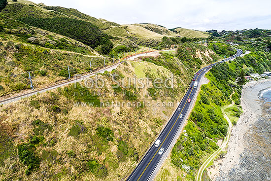 State Highway One (1) climbing above Pukerua Bay, with Main Trunk Railway Line and Escarpment Track above. Aerial view, Pukerua Bay, Porirua City District, Wellington Region, New Zealand (NZ) stock photo.