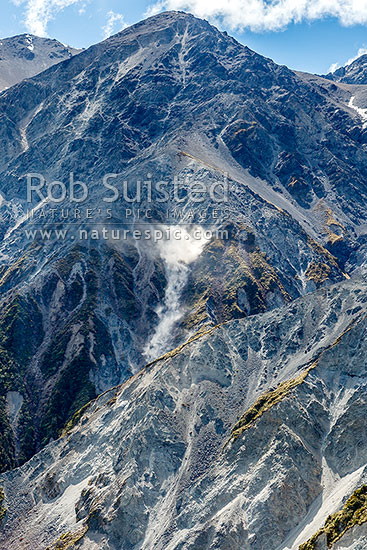 Rockfall happening on eroded mountain slopes. Seaward Kaikoura Ranges. Rock dust and debris lifted by falling rocks, Hapuku River, Kaikoura District, Canterbury Region, New Zealand (NZ) stock photo.