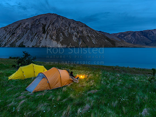 Tent camping by Lake Tennyson at dusk, with the light of a lantern. Lake Tennyson Scenic Reserve near the head of the Clarence River, inland Marlborough, Molesworth Station, Hurunui District, Canterbury Region, New Zealand (NZ) stock photo.