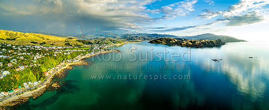 Plimmerton Beach and Porirua harbour entrance (centre), with Pauatahanui Inlet and rainbow distant left. Titahi Bay, Whitireia Park and Colonial Knob far right. Aerial panorama, Plimmerton, Porirua City District, Wellington Region, New Zealand (NZ) stock photo.