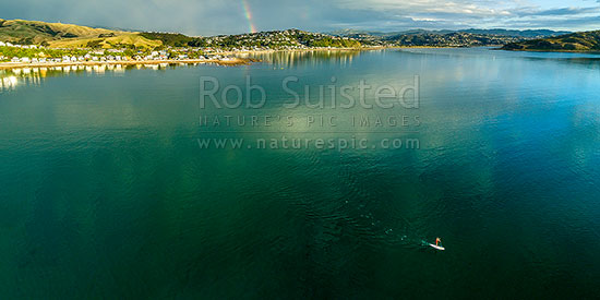 Stand up paddle boarder off Plimmerton and Karehana Beach. Porirua Harbour entrance far right. Rainbow. Aerial panorama, Plimmerton, Porirua City District, Wellington Region, New Zealand (NZ) stock photo.