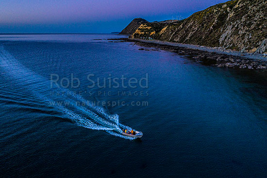 Makara Beach twilight with small boat returning into Ohariu Bay.  Mill Creek wind turbines above. Aerial view, Makara Beach, Wellington City District, Wellington Region, New Zealand (NZ) stock photo.