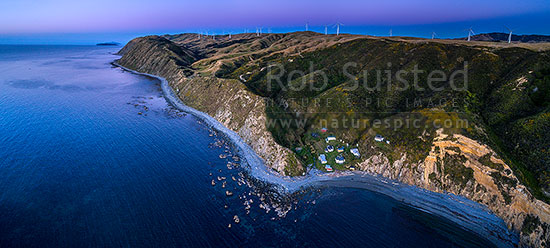 Mill Creek Wind Farm turbines above Smiths Bay and baches on the Makara Beach coastline. Looking north towards Mana and Kapiti islands in the sunset after glow. Aerial panorama, Makara Beach, Wellington City District, Wellington Region, New Zealand (NZ) stock photo.