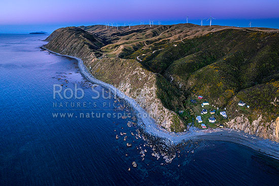 Mill Creek Wind Farm turbines above Smiths Bay and baches on the Makara Beach coastline. Looking north towards Mana and Kapiti islands in the sunset after glow. Aerial view, Makara Beach, Wellington City District, Wellington Region, New Zealand (NZ) stock photo.