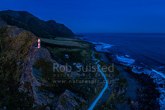 Cape Palliser, southern most point of the North Island (Matakitakiakupe). Cape Palliser Lighthouse shining in darkness with Aoraki Ranges (Haurangi Forest Park) beyond. Aerial view, Cape Palliser, South Wairarapa District, Wellington Region, New Zealand (NZ) stock photo.